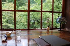 une table en plancher coller à la fenêtre de couleur marron foncer avec une lampe