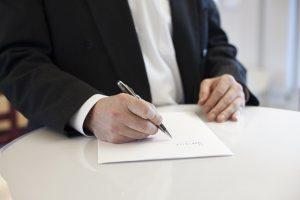 une personne qui signe un papier