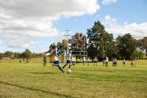 un joueur de foot qui va frappe le ballon et au loin y a deux équipe de football