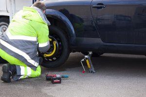 une personne change la roue de son véhicule